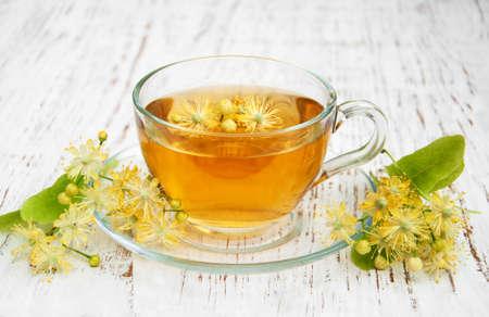 Foto de cup of herbal tea with linden flowers on a old wooden background - Imagen libre de derechos