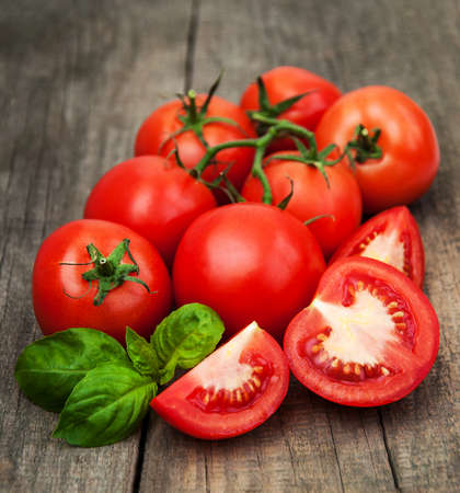 Photo for Fresh tomatoes with green basil on a old table - Royalty Free Image