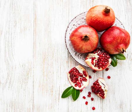 Foto de Juicy and ripe pomegranates in the plate  on old wooden table - Imagen libre de derechos