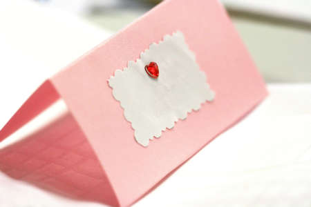 Photo for Blank pink wedding / greeting card with a red heart and copy space for text. - Royalty Free Image