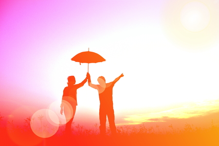 Silhouette women and man holding umbrella in the sunset