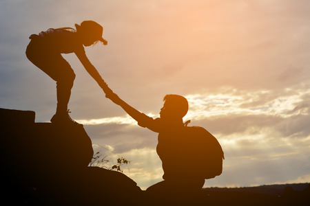 Foto de Silhouette of girl helps a boy on mountain at the sky sunset - Imagen libre de derechos