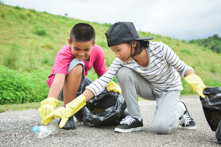 Foto de Children hands in yellow gloves picking up empty of bottle plastic into bin bag ,volunteer concept selective and soft focus - Imagen libre de derechos