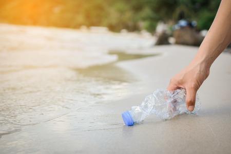 Photo pour Hand woman picking up plastic bottle cleaning on the beach , volunteer concept - image libre de droit