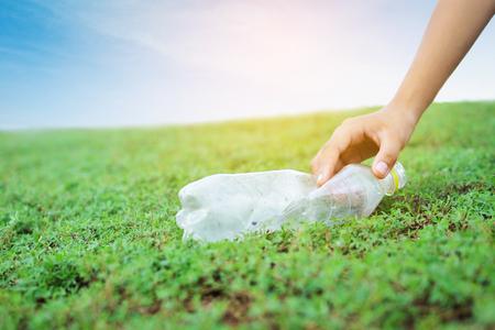 Foto de Hand picking plastic garbage on green grass - Imagen libre de derechos