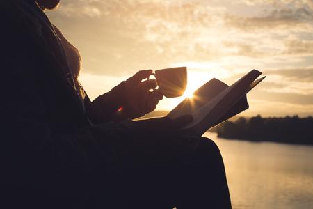Foto de Silhouette of happy old women reading a book sitting on the rock near lake waiting for sunset relax time and holiday, color vintage style selective and soft focus - Imagen libre de derechos