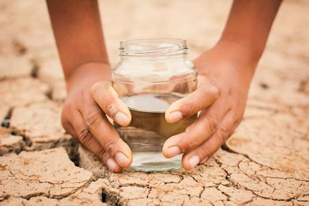 Foto de Hands of boy holding glass jar on cracked dry ground, concept drought and water crisis - Imagen libre de derechos