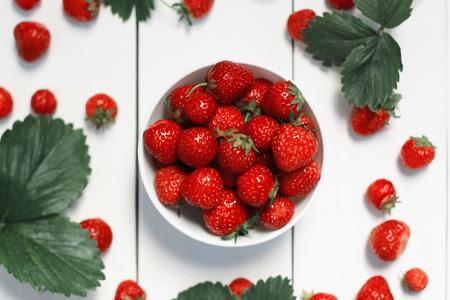 Foto de strawberry on a white wood background. selective focus on strawberries in the bowl - Imagen libre de derechos