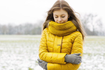 Photo for Pretty woman in a yellow knit scarf and yellow jacket. Outdoors portrait in the park. - Royalty Free Image