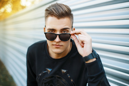 Photo for Young handsome man in stylish black clothes looking through sunglasses. - Royalty Free Image