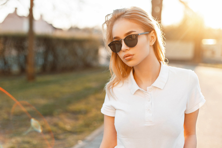 Photo pour Stylish young cute girl in sunglasses and white polo at sunset - image libre de droit