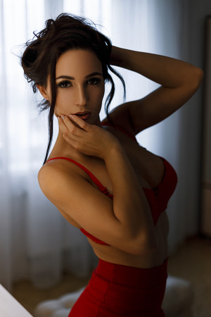 Photo pour Beautiful young girl with a hairstyle with a sexy silicone breast in a red bra and a red skirt in the room - image libre de droit