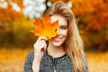 Foto de Beautiful happy woman with a smile holds an autumn yellow leaf near the face - Imagen libre de derechos