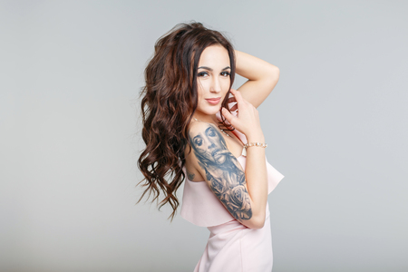 Photo pour Beautiful young woman with stylish tattoo on hand in pink dress on gray background - image libre de droit