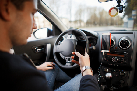 Photo for Man sits behind the wheel of a car and uses a smartphone. Travel - Royalty Free Image