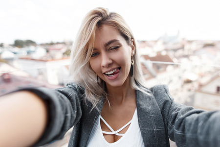 Photo pour Beautiful happy young fashionable girl shows tongue and makes selfie in the city. Woman is traveling and taking a photo on the phone. - image libre de droit