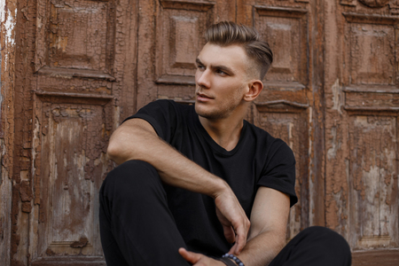 Foto de Handsome young american model man with hairstyle in black trendy t-shirt sitting near a vintage wooden door - Imagen libre de derechos