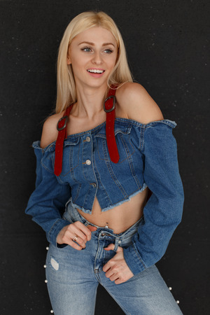Foto de Stylish pretty happy smiling woman with a smile in jeans clothes in blue jeans on a black background - Imagen libre de derechos