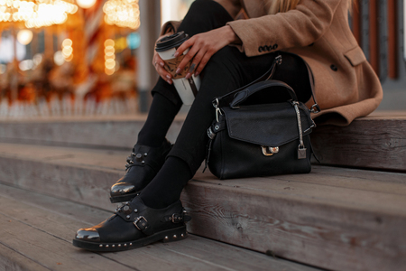 Photo pour Young hipster girl in an autumn vintage coat with stylish black jeans, in black leather fashionable modern shoes and with a small bag sits on the stairs with a cup of coffee. Women's legs with shoes - image libre de droit