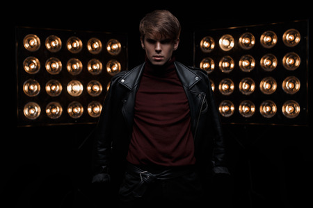 Photo for Young handsome fashionable man in a leather black jacket in burgundy golf in stylish pants posing in a dark studio against a background of bright electric vintage orange bulbs. Cute guy. Fashion. - Royalty Free Image