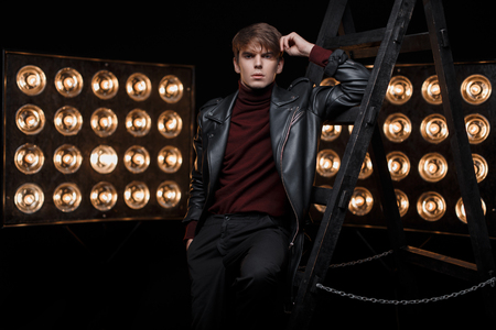 Photo for Fashionable young stylish guy in a red stylish golf in a vintage black jacket in black pants posing in the studio near the metal stairs against the background of bright yellow lamps.Fashionable guy - Royalty Free Image