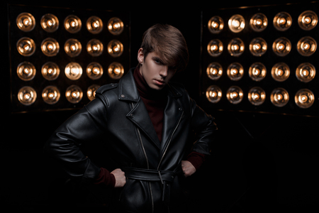 Photo for Young man with a haircut in a leather jacket in retro style in burgundy golf is standing and looking at the camera in the studio against the background of bright professional vintage lamp.Stylish guy - Royalty Free Image