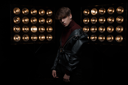 Photo for Sexy young stylish man in a stylish hairstyle in a leather fashionable jacket in burgundy golf poses for the camera in a dark room on the background of bright vintage electric lights. Nice guy - Royalty Free Image