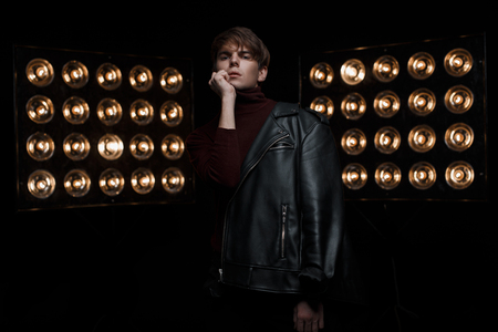 Photo for Attractive young man in a black trendy leather jacket in red stylish golf and black jeans stands and poses in a dark room near bright vintage electric professional lamps. Charming guy model - Royalty Free Image