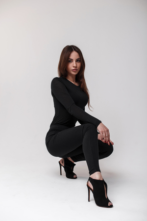 Foto de Cute young woman in a stylish T-shirt in stylish black leggings and leather stylish shoes with heels posing sit in the studio near the white wall. Fashionable sexy girl - Imagen libre de derechos