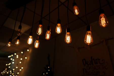 Photo for Orange-gold vintage incandescent bulbs hang in the room against the background of bright garlands and posters. Bright moments. A piece of interior - Royalty Free Image