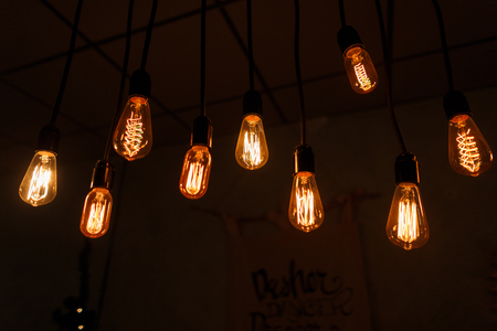 Photo for Yellow-orange vintage electric bright incandescent bulbs in retro style hang in a bar on a black background. A piece of interior. Festive decor. Close-up - Royalty Free Image