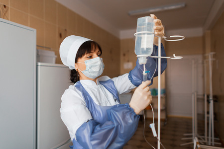 Foto de nurse anesthetist while in the hospital ward checks the counter drops. Doctor woman cares for the patient after the operation. Modern medicine - Imagen libre de derechos
