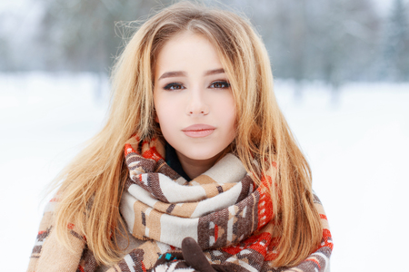 Foto de Portrait of a pretty young woman with brown eyes with beautiful makeup  with long blond hair in a woolen vintage warm scarf in a snowy park. Cute girl on a walk. - Imagen libre de derechos