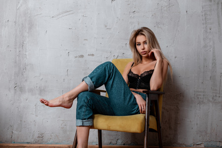 Foto de Charming attractive young woman with blond long hair with natural make-up in a luxurious black lace sconce in fashionable blue jeans poses on a vintage chair while sitting in a room. Elegant sexy girl - Imagen libre de derechos