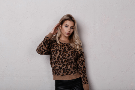 Foto de Slim glamorous young woman with long blond curly hair in a stylish leopard sweater in fashionable black leather pants posing in the studio near a white wall. Charming stylish girl. Women's fashion. - Imagen libre de derechos