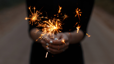 Foto de Amazing festive sparklers in the hands of a young woman. Girl celebrates happy birthday. Bright orange sparks with a close up. - Imagen libre de derechos