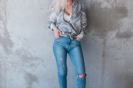Foto de Young sexy stylish woman in a summer fashionable shirt in ripped stylish jeans is standing near a gray concrete wall. Modern street style women's clothing. - Imagen libre de derechos