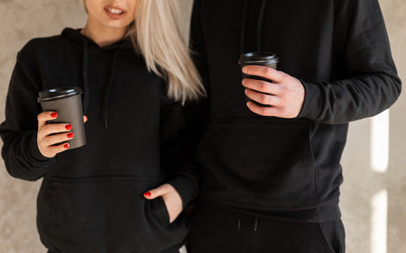 Foto de Young happy women blonde with a young stylish man with a beard in fashionable black clothes are standing near the wall indoors and holding coffee in hands. Coffee break. Close-up. - Imagen libre de derechos