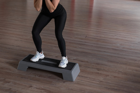 Foto de Young slim woman in sporty leggings in a black top in training in a gym crouches using a platform step. Girl coach shows exercises. Morning fitness. Close-up - Imagen libre de derechos