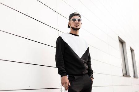 Photo pour American young hipster man in stylish black cap in trendy sunglasses in fashionable sport suit stand near a white wall in the city. Cool guy with a city on a street in the summer day. Youth style. - image libre de droit