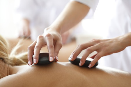 Foto de Young beautiful woman in spa getting hot stone massage - Imagen libre de derechos