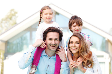 Photo pour happy family standing in front of the house - image libre de droit