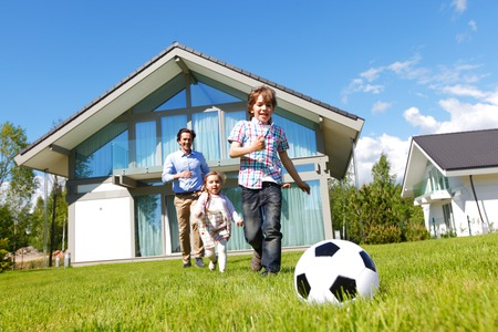 Photo pour family playing football in front of their house - image libre de droit