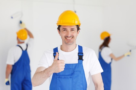 Photo for workman gives thumbs up in front of two painters - Royalty Free Image