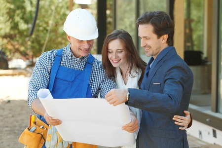 Photo for foreman shows house design plans to a young couple - Royalty Free Image