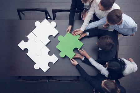 Foto de Group of business people assembling jigsaw puzzle, team support and help concept - Imagen libre de derechos