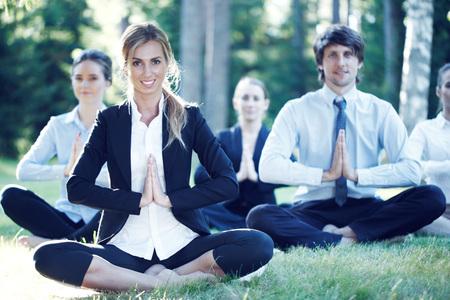 Photo pour Business people practicing yoga in park - image libre de droit
