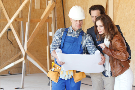 Photo pour Foreman shows house design plans to a young couple - image libre de droit