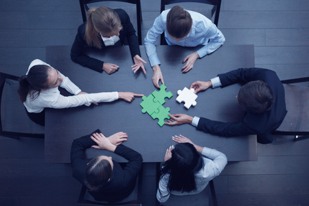 Photo pour Group of business people assembling jigsaw puzzle, team support and help concept - image libre de droit