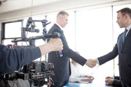 Foto de Videographer using steadycam, making video of business people shaking hands - Imagen libre de derechos